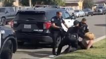 Un policía golpea en el rostro a una mujer hispana mientras la tiene esposada