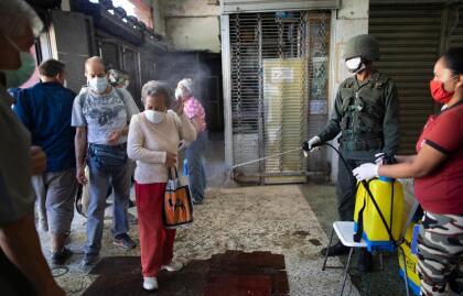 <b>Desinfección militar.</b> Un soldado rocía a los clientes de una tienda de alimentos con una solución desinfectante a base de cloro en Caracas, Venezuela, el 20 de marzo. En ese país se han registrado más de 70 casos de covid-19.