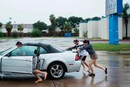 People push a disabled car during the aftermath of Hurricane Harvey August 27, 2017 in Houston, Texas. Hurricane Harvey left a trail of devastation Saturday after the most powerful storm to hit the US mainland in over a decade slammed into Texas, destroying homes, severing power supplies and forcing tens of thousands of residents to flee. / AFP PHOTO / Brendan Smialowski (Photo credit should read BRENDAN SMIALOWSKI/AFP/Getty Images)