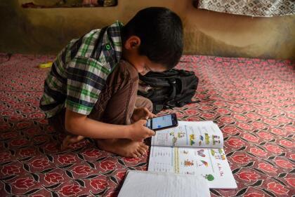 """<b>Un teléfono móvil y un libro</b>. Un estudiante de Cachemira escucha a su maestro durante una clase en línea a través de la aplicación Zoom el 1 de mayo. Los estudiantes en esta región han sufrido los bloqueos de la señal de internet,  <a href=""""https://www.univision.com/noticias/premio-pulitzer-2020-imagenes-de-represion-y-violencia-se-llevan-el-maximo-galardon-del-periodismo-estadounidense-fotos"""">una consecuencia del conflicto político y militar en la región</a>."""