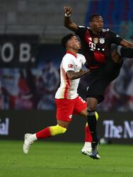 LEIPZIG, GERMANY - APRIL 03: David Alaba of FC Bayern Muenchen jumps for the ball under pressure from Justin Kluivert and Willi Orban of RB Leipzig during the Bundesliga match between RB Leipzig and FC Bayern Muenchen at Red Bull Arena on April 03, 2021 in Leipzig, Germany. Sporting stadiums around Germany remain under strict restrictions due to the Coronavirus Pandemic as Government social distancing laws prohibit fans inside venues resulting in games being played behind closed doors. (Photo by Filip Singer - Pool/Getty Images)