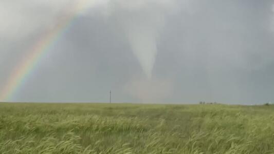Fantástica vista de un tornado y un arcoíris en el horizonte de una pradera