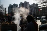 In this picture taken on December 13, 2017, a man buys steamed buns from a street vendor on a cold day in Baoding. As temperatures dipped below freezing in a northern Chinese village, a group of parka-clad women tried to stay warm as they played mahjong around a small gas stove in a grocery store. / AFP PHOTO / FRED DUFOUR / To go with AFP story China-Energy-Pollution , Focus by Julien Girault (Photo credit should read FRED DUFOUR/AFP via Getty Images)