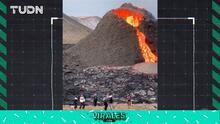 Jóvenes juegan voleibol con el volcán en erupción de fondo