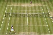 Slovakia's Magdalena Rybarikova , top, serves to Spain's Garbine Muguruza, during their Women's Singles semifinal match on day nine at the Wimbledon Tennis Championships in London Thursday, July 13, 2017. (Tony O'Brien/Pool Photo via AP)