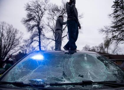 BROOKLYN CENTER, MN - APRIL 11: People stand on a police cruiser as protesters take to the streets after Brooklyn Center police shot and killed Daunte Wright during a traffic stop on April 11, 2021 in Brooklyn Center, Minnesota. A crowd gathered to confront police as they held a line while investigators searched the scene. (Photo by Stephen Maturen/Getty Images)