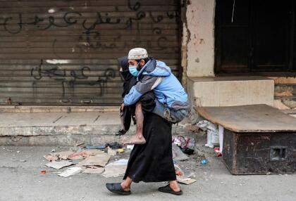 <b>Refugiados protegidos.</b> Una mujer lleva en su espalda a un hombre con una máscara contra el coronavirus en un campo de refugiados palestinos al sur de Beirut, Líbano. 22 de marzo.