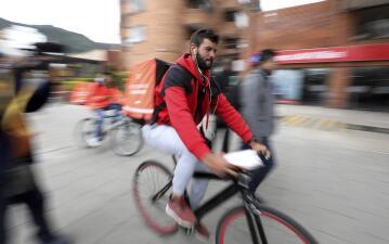 Pedalear para sobrevivir: venezolanos se ganan la vida en Colombia con una aplicación multimillonaria de entregas en bicicleta (fotos)