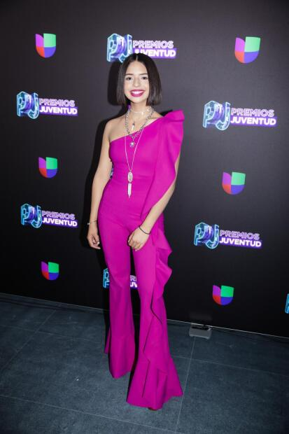 La mexicana  <b>Ángela Aguila</b>r llevó un jumpsuit fucsia de escote asimétrico y vuelos a un lado.
