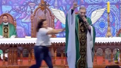 (Video) Mujer irrumpe en medio de una misa y empuja al sacerdote contra el público